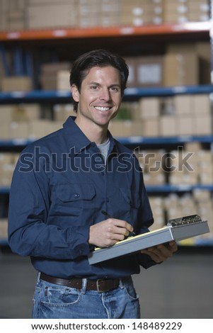 Portrait of a young man working in distribution warehouse - stock photo
