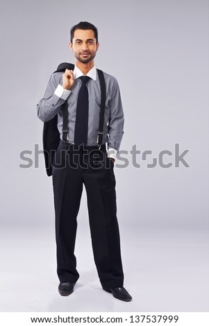Portrait of a young manager holding a coat over his shoulder - stock photo