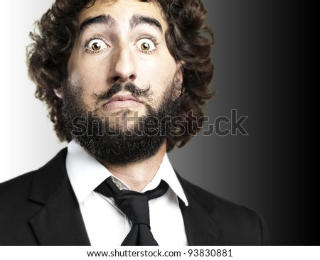 portrait of a young mans face afraid against a black background - stock photo