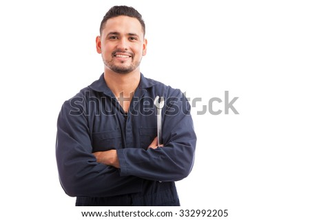 Portrait of a young mechanic holding a wrench and smiling, ready to fix cars - stock photo