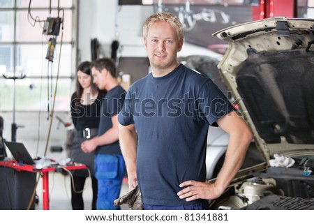 Portrait of a  young mechanic in auto repair shop with customer in background - stock photo