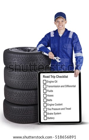 Portrait of a young mechanic is showing information about road trip on the board while standing with stack of tires in the studio