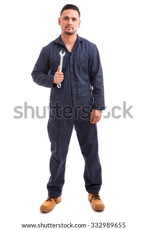 Portrait of a young mechanic wearing overalls and holding a wrench at work on a white background - stock photo