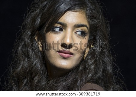 Portrait of a young middle eastern woman looking over her shoulder - stock photo