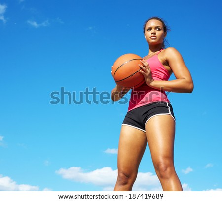 Portrait of a young mixed race female holding basketball.