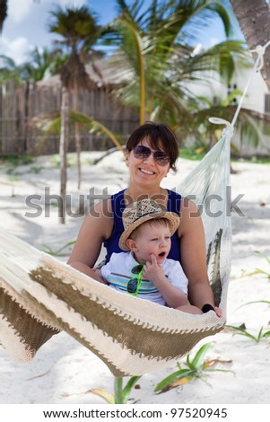 Portrait of a young mother and a cute toddler boy on a tropical beach - stock photo