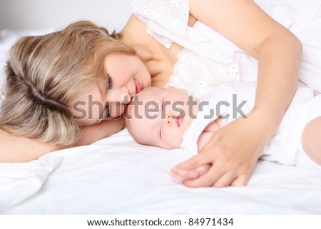 Portrait of a young mother and baby and a girl in her arms - stock photo