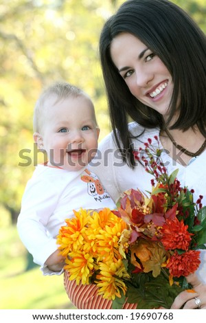 Portrait of a young mother and her blue-eyed baby boy with bright orange and yellow flowers, outdoors in a park, suitable for a variety of seasonal and family themes - stock photo