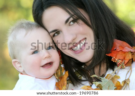 Portrait of a young mother and her blue-eyed baby boy with bright orange and yellow leaves, outdoors in a park, suitable for a variety of seasonal and family themes