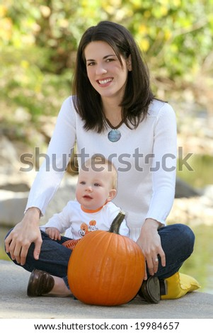 Portrait of a young mother and her blue-eyed baby boy with bright orange pumpkin, outdoors in a park, suitable for a variety of seasonal and family themes
