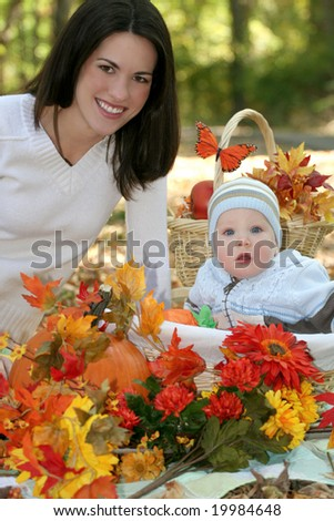 Portrait of a young mother and her blue-eyed baby boy with fall leaves, pumpkins and bright flowers, outdoors in a park, suitable for a variety of seasonal and family themes