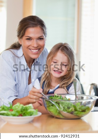 Portrait of a young mother and her daughter preparing a salad in their kitchen - stock photo