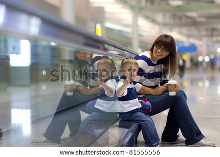 Portrait of a young mother and her son waiting for a flight at an international airport - stock photo