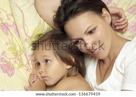Portrait of a young mother and little daughter in bed at home