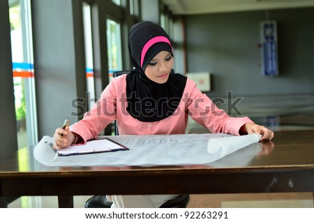 Portrait of a young Muslim architect-woman busy at work