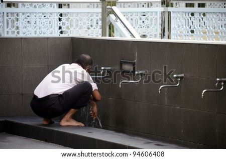 Portrait of a young Muslim man perform ablution (wudhu)  before prayer - stock photo