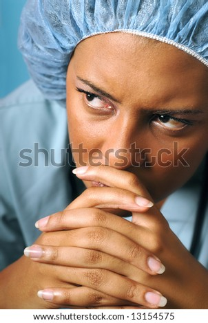 Portrait of a young nurse looking unhappy and tired - stock photo