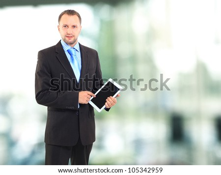 Portrait of a young office worker using a tablet computer in his office - stock photo