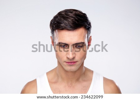 Portrait of a young pensive man over gray background - stock photo