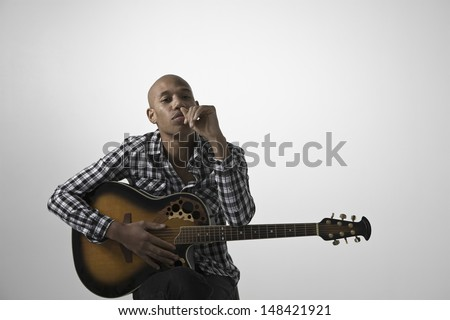 Portrait of a young pensive man with guitar sitting against gray background
