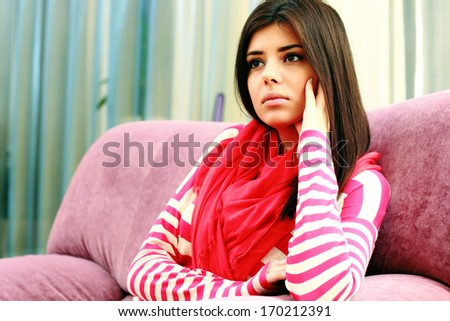 Portrait of a young pensive woman sitting on the sofa at home - stock photo