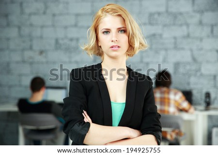 Portrait of a young pensive woman standing with arms folded in office