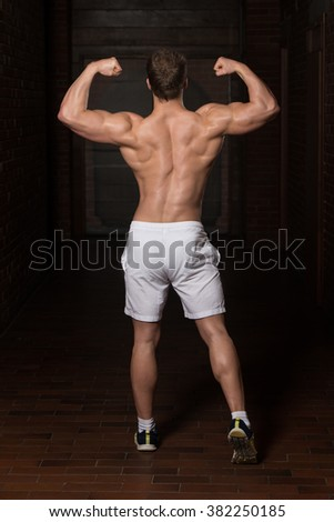Portrait Of A Young Physically Fit Man Showing His Well Trained Body - stock photo