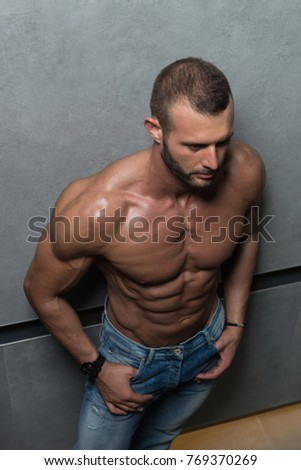 Portrait of a Young Physically Fit Man Showing His Well Trained Body While Wearing Blue Jeans - Muscular Athletic Fitness Model Posing After Exercises on Wall Near the Wall - a Place for Your Text