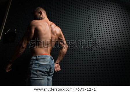 Portrait of a Young Physically Fit Man Showing His Well Trained Body While Wearing Blue Jeans - Muscular Fitness Model Posing After Exercises on Wall Near the Wall - a Place for Your Text