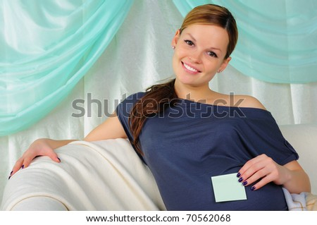 Portrait of a young pregnant girl on a light background