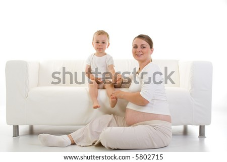Portrait of a young pregnant woman with a toddler...predominant color is white. - stock photo
