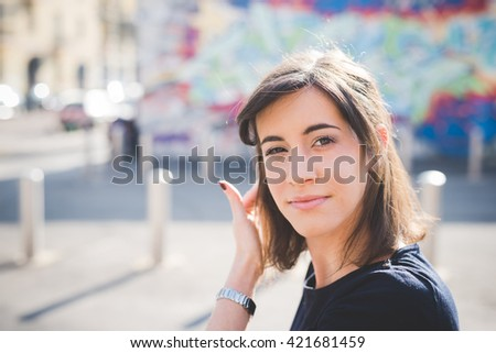 Portrait of a young pretty brown hair caucasian girl looking in camera touching her hair, pensive - relax, carefree concept