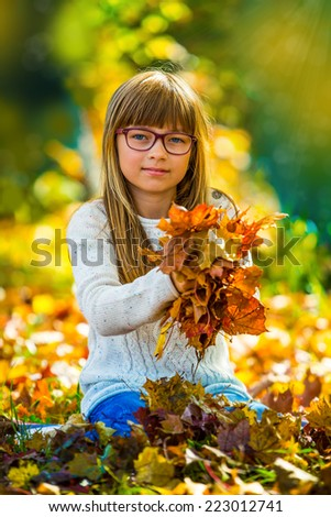 Portrait of a young pretty girl who was cheerfully playing with autumn maple leaves.Girl sitting on colorful autumn leaves and holding in his hand a bouquet of maple leaves - stock photo