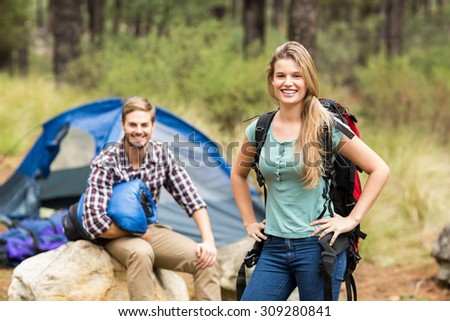 Portrait of a young pretty hiker couple holding a sleeping bag and backpack in the nature - stock photo