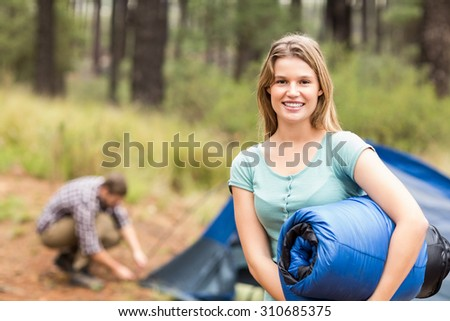 Portrait of a young pretty hiker holding a sleeping bag in the nature - stock photo