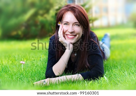 portrait of a young pretty smiling woman lying on green grass in the meadow  in summer - stock photo