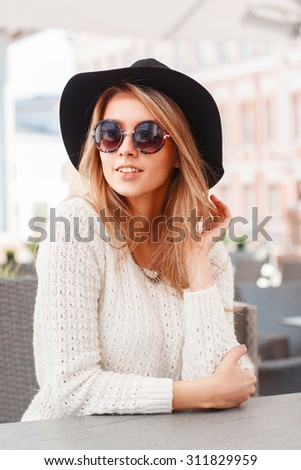 Portrait of a young pretty woman in a black hat and round sunglasses. Beautiful girl sits in summer cafe. - stock photo