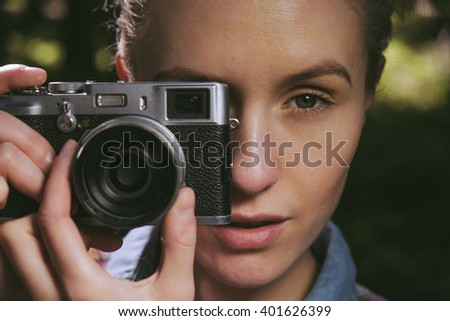 portrait of a young pretty woman looking through a vintage looking rangefinder camera