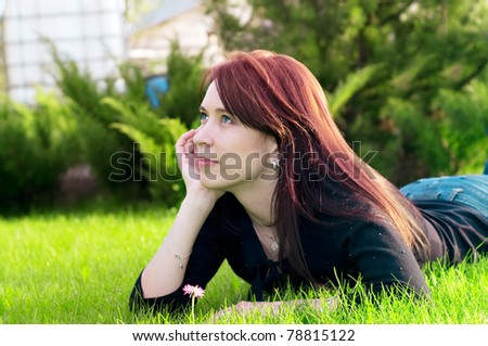 portrait of a young pretty woman lying on green grass in the meadow - stock photo