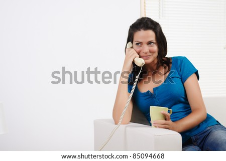 Portrait of a  young pretty woman on the phone and smiling. - stock photo