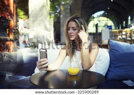 Portrait of a young pretty woman posing for make self portrait for social network picture while she sitting in cafe, charming latin female photographing herself with smart phone digital camera