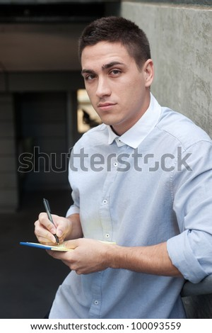 Portrait of a young professional man standing outside a building holding pen and paper