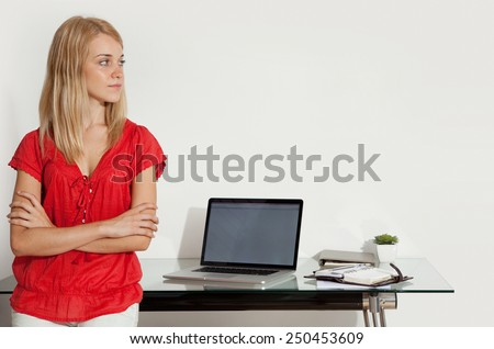 Portrait of a young professional woman in her home office space with her arms crossed, looking away. Student girl using a laptop computer at her home work desk. Lifestyle and technology, interior. - stock photo
