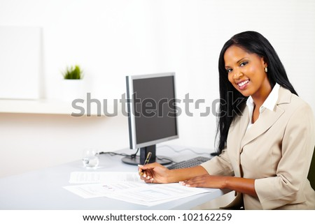 Portrait of a young professional woman on work desk, smiling and looking to you whole working on documents