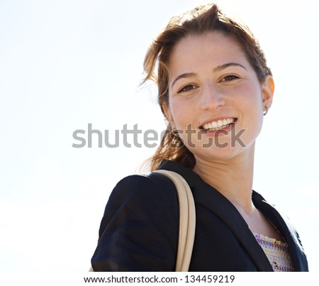Portrait of a young professional woman wearing a black suit jacket and smiling at the camera against a sunny sky.
