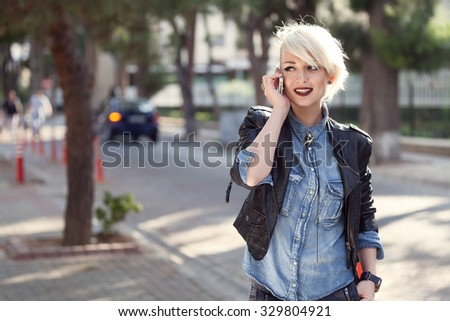 portrait of a young punk style blond woman outdoor, talking with her mobile phone - stock photo