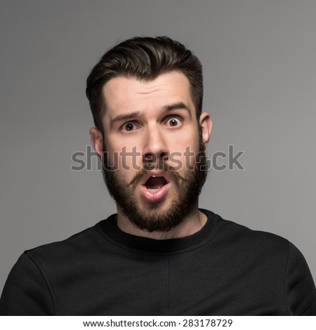 Portrait of a young puzzled businessman with opened mouth on gray background - stock photo