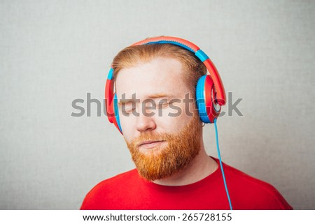 Portrait of a Young  red bearded Man singing and listening to music in headphones