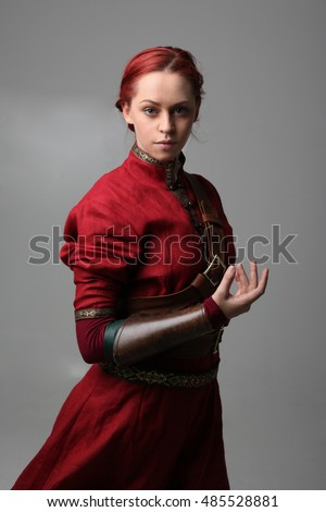 portrait of a young  red haired  female warrior,  wearing a red medieval tunic and leather Armour.  grey background.
