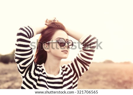 Portrait of a young redhead girl in sunglasses and striped sweater at outdoor in autumn time - stock photo